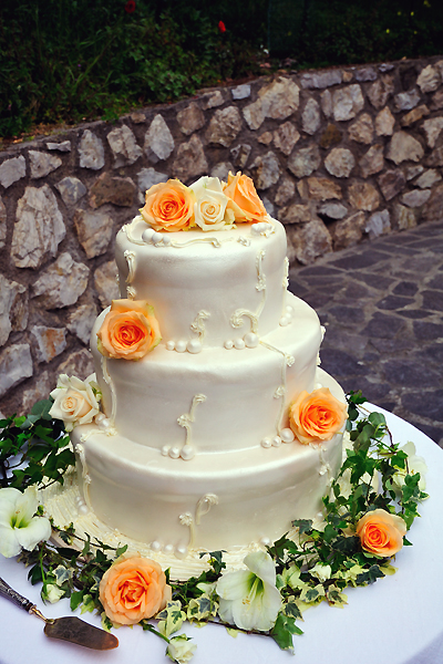 Layered wedding cake covered with a shell of frosting dense with roses and ivy garlands
